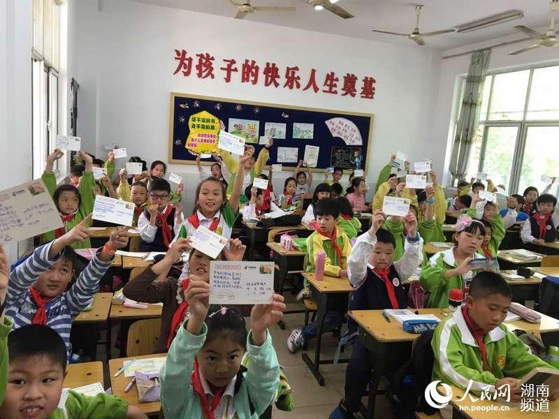 常德邮政组织北正街小学学生亲手为结对帮助的农村留守儿童书写邮政明信片