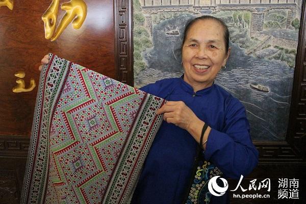 69岁的织娘石培云展示侗锦