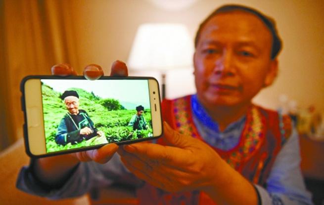 龙献文在驻地展示手机中家乡茶园的照片